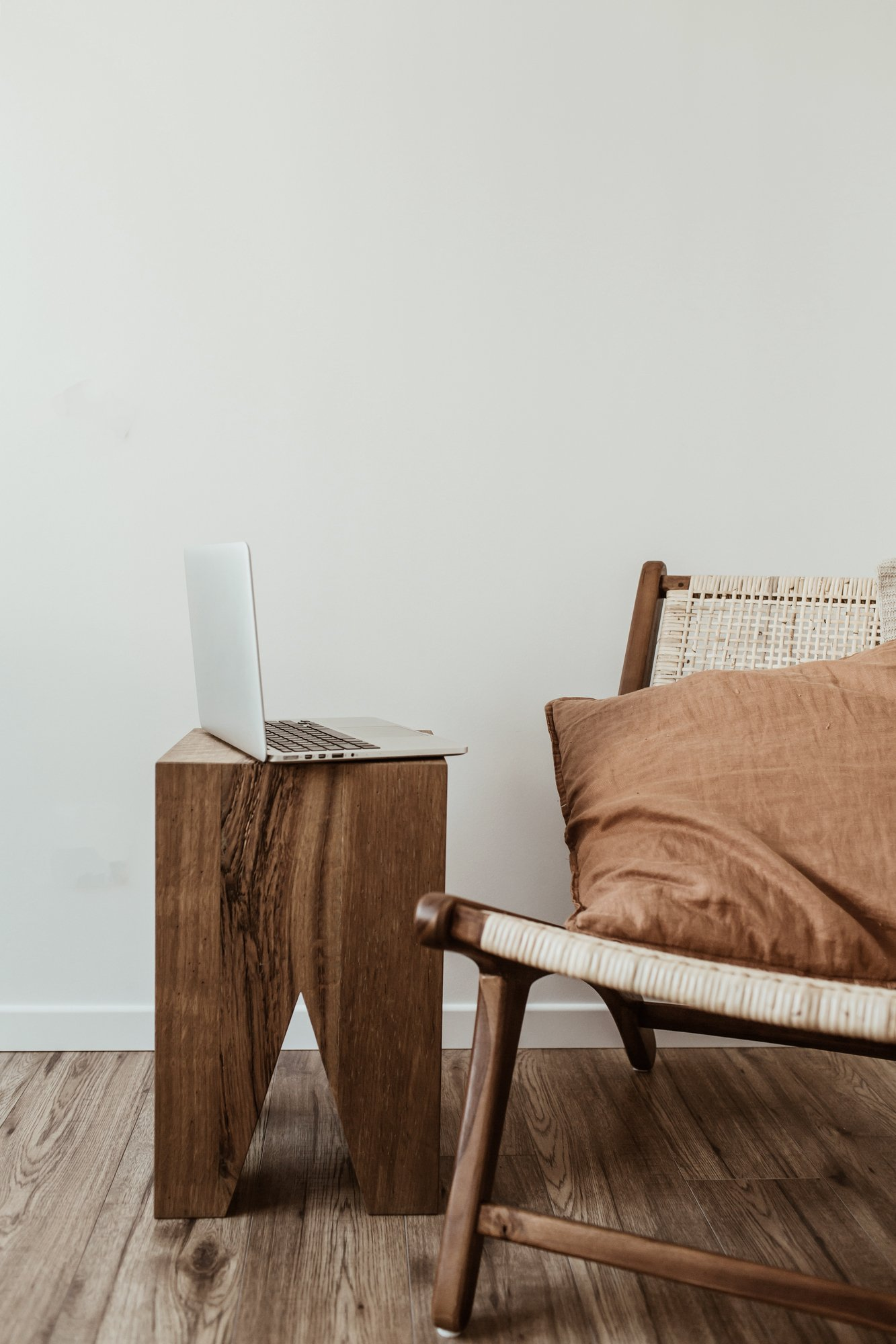 Modern interior design concept. Stylish rattan wooden chair, knitted plaid, ginger pillow. Home office workspace with laptop.