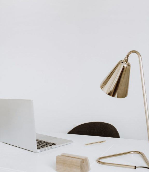 Modern minimal interior design concept. Bright Scandinavian home office desk table workspace with laptop, lamp. Business study cabinet. Girl boss studio concept.